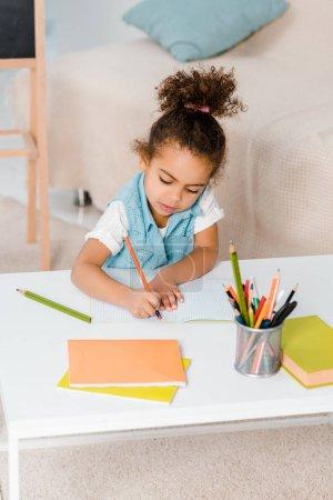 Photo pour Vue d'angle élevé de mignonne enfant afro-américain assis et écrit avec un crayon - image libre de droit