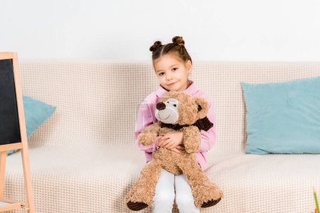 Photo for Beautiful kid sitting on sofa with teddy bear and smiling at camera - Royalty Free Image
