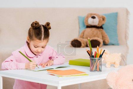 Photo pour Adorable enfant concentré écriture avec crayon et étudier à la maison - image libre de droit