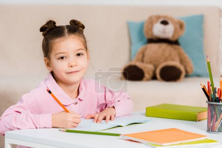 Photo for Cute kid writing with pencil and smiling at camera while studying at home - Royalty Free Image