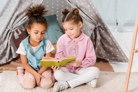 high angle view of cute multiethnic kids sitting on carpet and reading book together