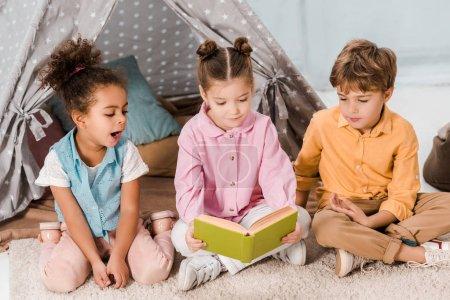 Photo pour Mignons petits enfants assis sur le tapis et le livre de lecture ensemble - image libre de droit