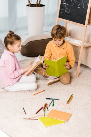 high angle view of adorable focused kids sitting on carpet and reading books together
