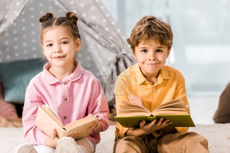 beautiful children holding books and smiling at camera together