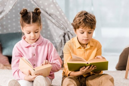 Photo for Adorable kids sitting on carpet and reading books together - Royalty Free Image