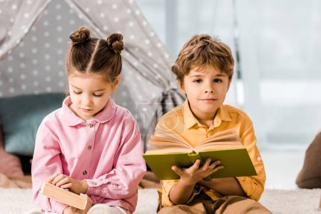adorable little children reading books together