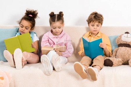 Photo pour Adorables enfants multiethniques assis sur le canapé et lisant des livres ensemble - image libre de droit