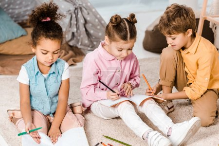 adorable multiethnic children sitting on carpet and studying together