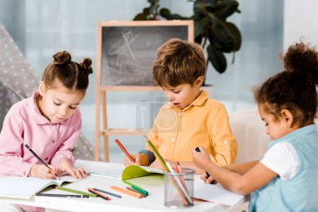 adorable little multiethnic kids drawing and studying together