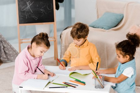 beautiful little multiethnic kids drawing and studying together