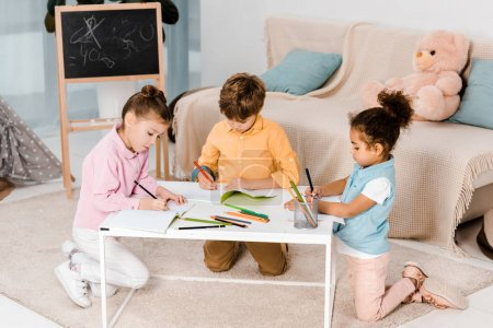 high angle view of adorable multiethnic children drawing and studying together