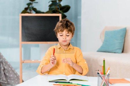 Photo pour Mignon enfant tenant stylo et étudier à la maison - image libre de droit
