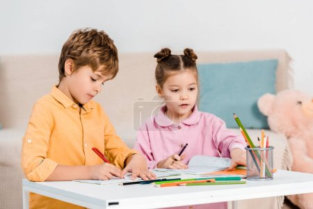 Photo for Adorable little children writing and studying together - Royalty Free Image
