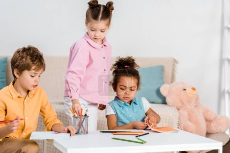 adorable multiethnic children drawing and studying together