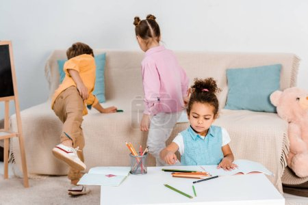 high angle view of adorable multiethnic children playing and drawing together