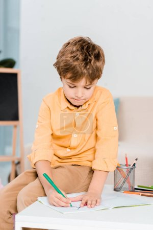 Photo for Focused little boy writing and studying at home - Royalty Free Image