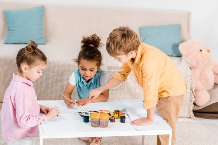 high angle view of adorable multiethnic children drawing with paints and brushes