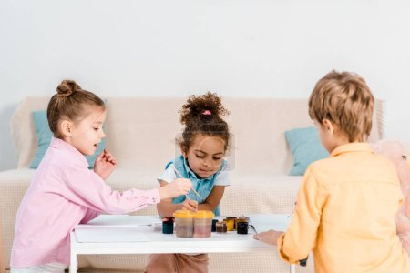 adorable multiethnic children sitting and drawing together
