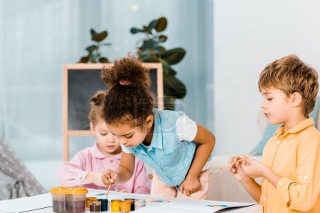 beautiful little multiracial children painting together