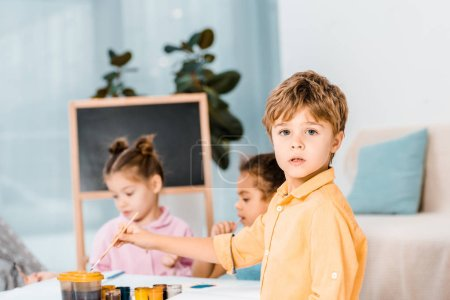 adorable little boy looking at camera while painting with friends
