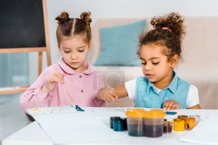 cute little multiethnic kids sitting and painting together