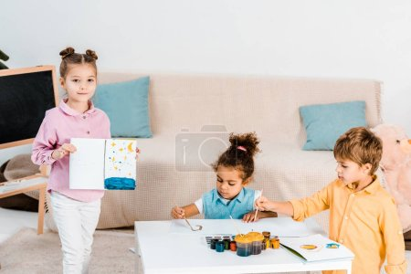 adorable multiethnic children drawing with paints together