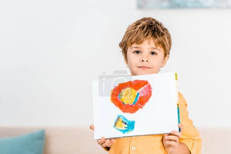 adorable little boy holding picture and looking at camera