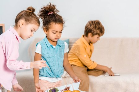 adorable multiethnic kids drawing with paints together