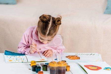 Foto de Adorable niño enfocado sentado y pintar cuadro - Imagen libre de derechos