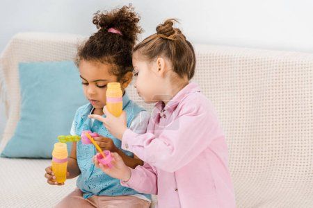 adorable multiethnic children sitting on sofa and blowing soap bubbles