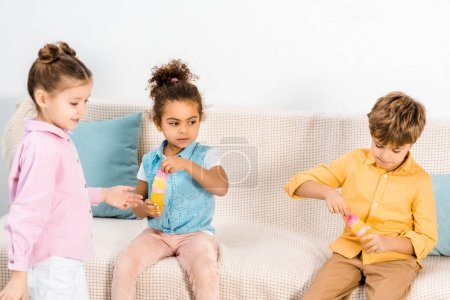 cute multiethnic children playing with soap bubbles together