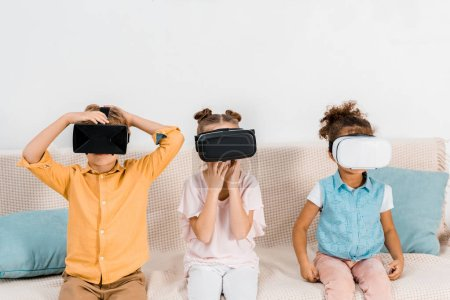 adorable multiethnic children sitting in sofa and using virtual reality headsets