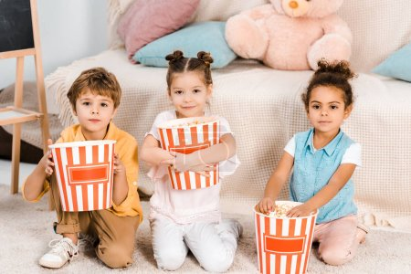 Photo for Adorable multiethnic kids holding boxes with popcorn and looking at camera - Royalty Free Image