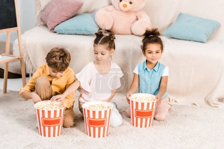 high angle view of cute multiethnic kids sitting on carpet and eating popcorn from boxes