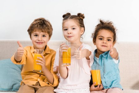cute multiethnic kids holding glasses of juice and showing thumbs up