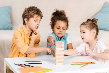Photo for Cute focused children building tower from wooden blocks on table - Royalty Free Image