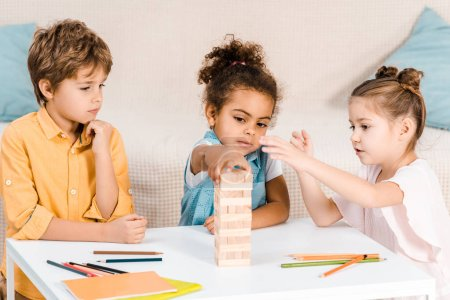 adorable multiethnic kids building tower from wooden blocks on table
