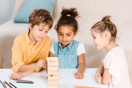 cute happy children building tower from wooden blocks on table