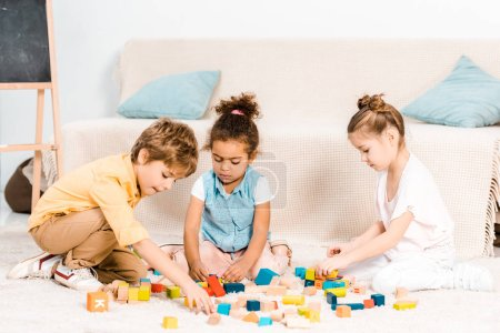 cute little children playing with colorful cubes on carpet