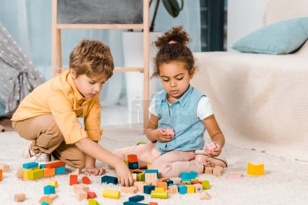 adorable multiethnic kids playing with colorful wooden blocks on carpet