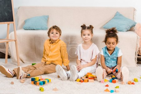 adorable multiethnic kids playing with colorful cubes and smiling at camera