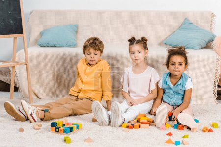 cute multiethnic kids playing with colorful cubes and looking at camera