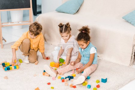 high angle view of adorable multiethnic kids playing with colorful cubes on carpet