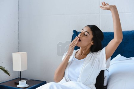 beautiful mixed race girl in white robe yawning and covering mouth in morning in bedroom