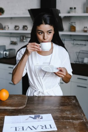 beautiful mixed race girl in white robe drinking coffee in morning in kitchen