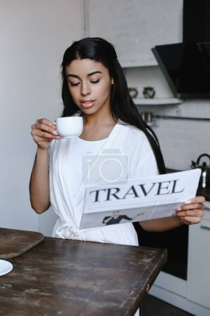 beautiful mixed race girl in white robe holding cup of coffee and reading travel newspaper in morning in kitchen