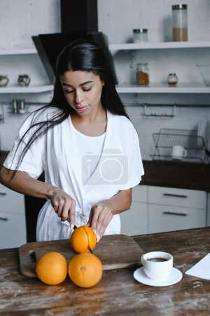 Photo for Beautiful mixed race girl in white robe preparing orange juice in morning and cutting oranges in kitchen - Royalty Free Image