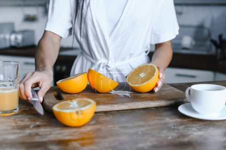 Photo for Cropped image of mixed race girl in white robe preparing orange juice in morning and cutting oranges in kitchen - Royalty Free Image