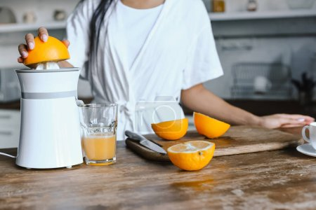 Photo for Cropped image of mixed race girl in white robe preparing orange juice in morning in kitchen - Royalty Free Image