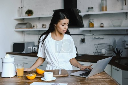 Photo pour Fille séduisante métisse en robe blanche en utilisant l'ordinateur portable dans la matinée en cuisine - image libre de droit
